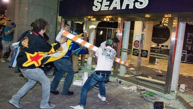 Rioters break the front doors of a Sears department store on Granville Street during the 2011 Stanley Cup riot in downtown Vancouver. Three of the suspected rioters have been tracked to the U.S., according to Vancouver police.