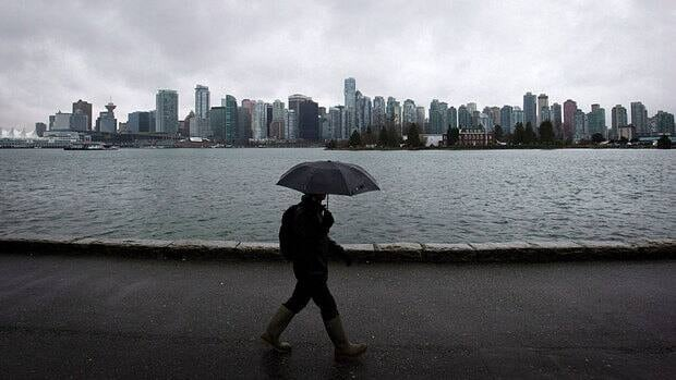 A man shields himself from the rain with an umbrella as he walks along the Stanley Park seawall in Vancouver.