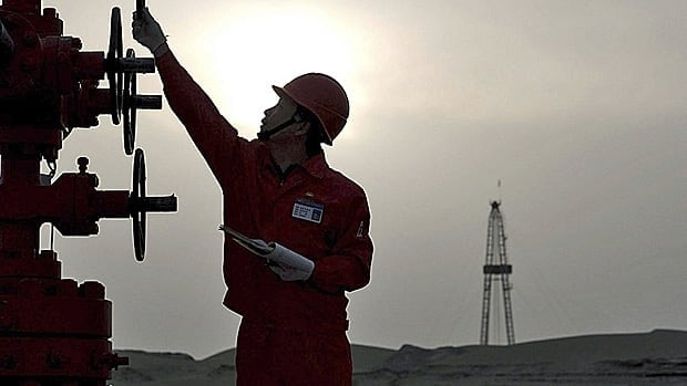 A Petrochina worker checks pipes at the company Tarim Oilfield in Taklamakan Desert in Xinjiang. The company bought the remaining stake in the MacKay River oilsands project Tuesday.