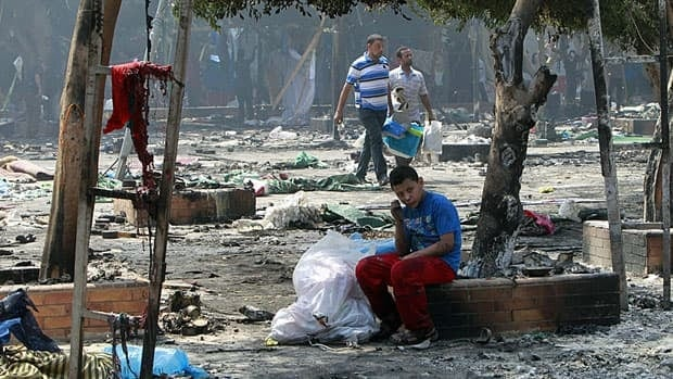 A young Muslim Brotherhood supporter sits among the wreckage outside the burnt Rabaa Adawiya mosque in Cairo on Thursday after security forces used bulldozers and tear gas to clear the demonstration site.