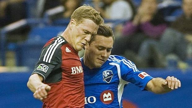 Toronto FC's Ty Harden, left, battles for the ball in a loss to Andrew Wenger and the Montreal Impact last week, dropping the team to 0-4. Harden says they still believe in themselves.
