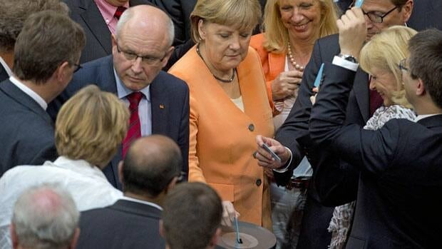 German Chancellor Angela Merkel, center, and fellow parliamentarians cast their vote on a rescue package for Spain's ailing banks during special session of the German parliament in Berlin Thursday.