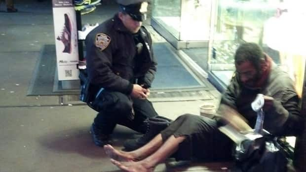 New York City police officer Larry DePrimo gives a homeless man all-weather boots on Nov. 14, 2012.  The man was discovered in Manhattan over the weekend wandering without shoes again.