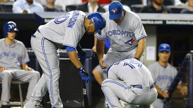 Jose Bautista of the Toronto Blue Jays (19) in pain after hurting his wrist swinging the bat during the game against the New York Yankees.