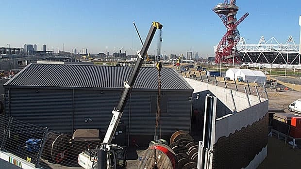 A crane hoists a spool of cabling at London's Olympic Park on March 19, 2012. The organizing committee of the 2012 London Games is drawing the ire of techies for its attempt to police the use of portable WiFi hotspots and 3G hubs at Olympic venues.