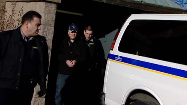 Canadian naval intelligence officer Jeffrey Paul Delisle, centre, is led out of court Monday. The Halifax man is accused under the Security of Information Act of passing secrets to a foreign entity.