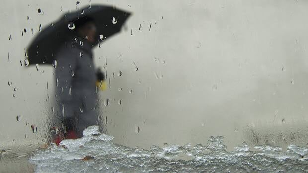 A woman, seen through a window, takes cover with her umbrella as both snow and rain fall in the streets of Toronto on Friday, Feb. 24, 2012.