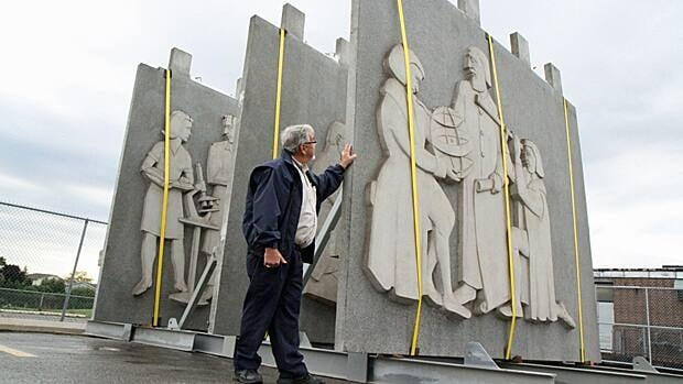 John Aikman, manager of the Hamilton-Wentworth District School Board archives, stands next to three panels that formed the frieze above the Education Centre entrance. (Samantha Craggs/CBC)