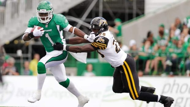 Saskatchewan Roughriders running back Kory Sheets gets tackled by Hamilton Tiger-Cats linebacker Jamall Johnson during the first half in Regina, Sask., on Sunday.
