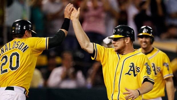 Oakland's Brandon Moss, right, celebrates with Josh Donaldson after both scored against the Texas Rangers in the fifth inning.