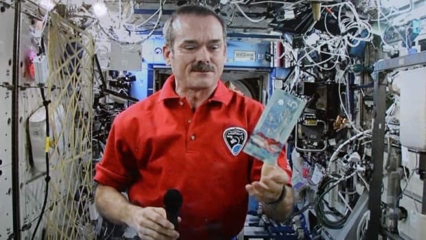 Astronaut Chris Hadfield poses for a photo with a new polymer $5 bank note aboard the International Space Station.