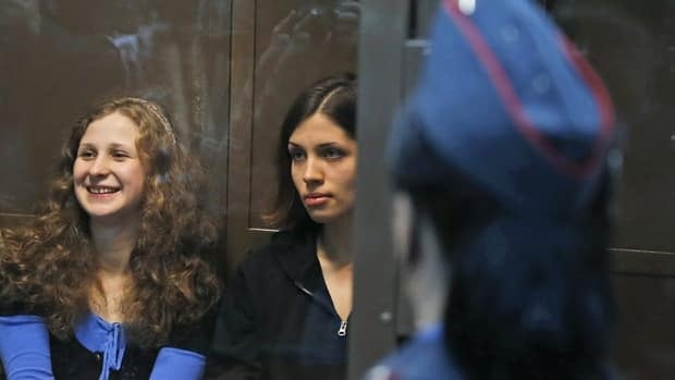 Maria Alekhina and Nadezhda Tolokonnikova sit in a glass cage in a court room in Moscow earlier this month.