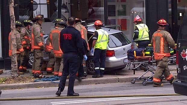 Firefighters attend to the driver of a vehicle that crashed into a King Street storefront.
