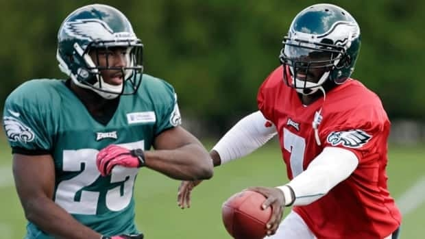 Philadelphia Eagles quarterback Michael Vick, right, hands off the ball to running back LeSean McCoy at the team's NFL football training facility, Wednesday, Oct. 10, 2012, in Philadelphia.