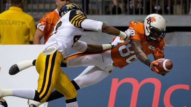 B.C. Lions' Courtney Taylor, right, dives for the goal line but is shoved out of bounds by Hamilton Tiger-Cats' Raymond Brown during the first half of a CFL football game in Vancouver, B.C., on Friday.