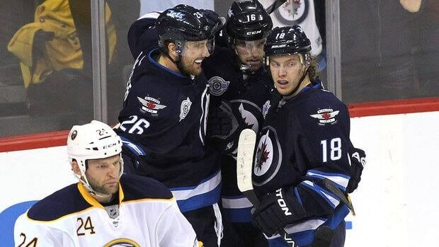 Blake Wheeler (26 )and Bryan Little (18) of the Winnipeg Jets celebrate a goal by captain Andrew Ladd (16) against the Buffalo Sabres on Monday.