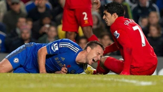 Chelsea's John Terry, left reacts after being injured, after a tackle by Liverpool's Luis Suarez, in London, Sunday. Terry was carried from the pitch on a stretcher shortly after the incident.
