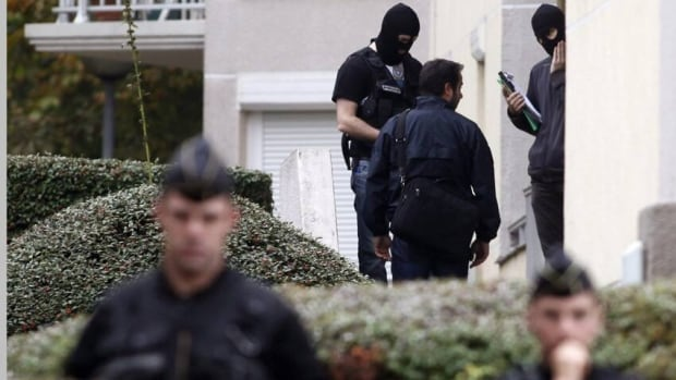 French police officers converse Wednesday outside a building where authorities discovered bomb-making material last week, in Torcy, east of Paris.