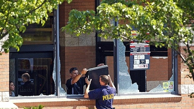 Police officers remove a computer hard drive from a Pathmark supermarket in Old Bridge, N.J. where an employee opened fire on employees.