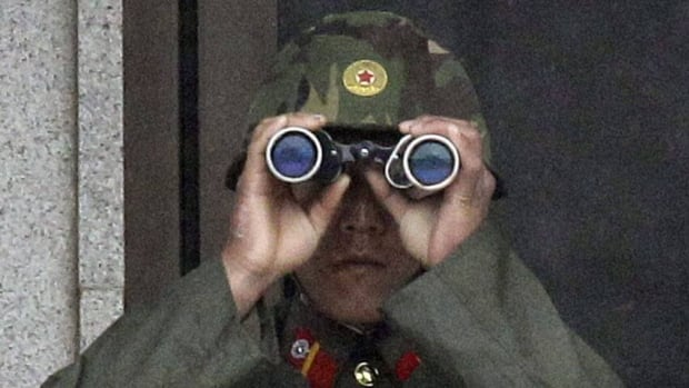 "A North Korean soldier looks at the southern side through binoculars at the Demilitarized Zone in April. On Friday, North Korea said it had detained a U.S. citizen whose crimes were ""proven by evidence"""