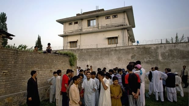 Local residents gather outside the house in Pakistan where al-Qaeda leader Osama bin Laden was caught and killed last May. Two residents said Saturday the Pakistani government is demolishing the compound.