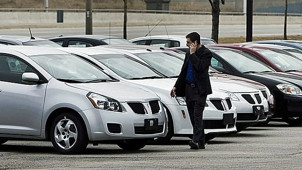 A man walks past cars at a General Motors dealership in Toronto. There was a 2.7 per cent drop in new car sales in December, Statistics Canada says. (Nathan Denette/Canadian Press)