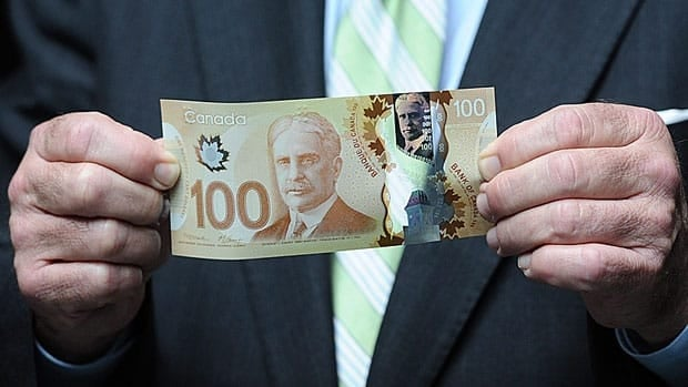 Finance Minister Jim Flaherty holds a new polymer-based $100 bill. The Bank of Canada heard some odd interpretations of the security features and images on the new $100 and $50 bills from members of a focus group.