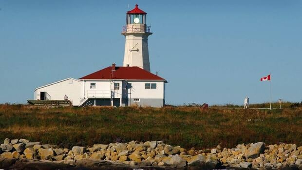 The Canadian flag flutters in the breeze by the lighthouse at Machias Seal Island.