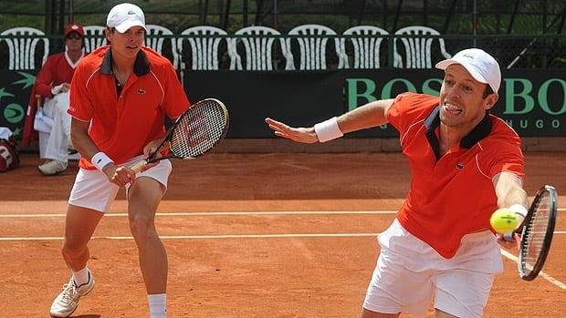 Daniel Nestor, right, returns the ball alongside teammate Milos Raonic during their Davis Cup doubles tennis match.