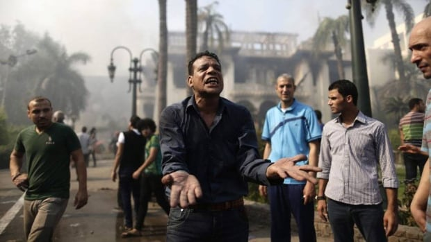 An Egyptian man reacts as firefighters battle flames at the Giza governorate buildings that were stormed and torched by angry supporters of Egypt's ousted president. Egypt faced a new phase of uncertainty on Thursday after the bloodiest day since its Arab Spring began, with hundreds of people reported killed and thousands injured as police smashed two protest camps of supporters of the deposed Islamist president. Wednesday's raids touched off day-long street violence that prompted the military-backed interim leaders to impose a state of emergency and curfew, and drew widespread condemnation from the Muslim world and the West, including the United States.