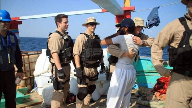 An Iranian fisherman embraces a U.S. sailor on Thursday, following a mission in which members of the U.S. Navy rescued Iranian crew members whose fishing dhow was seized by suspected Somali pirates.