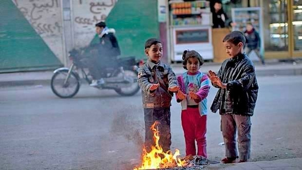 Children warm their hands by a fire in Idlib, north Syria, on Monday. Syrian refugees fleeing to neighboring Lebanon said they feared they would be slaughtered in their own homes as government forces hunted down opponents in a brutal offensive against the opposition stronghold of Homs.