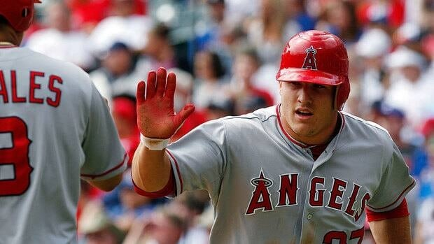 Angels' Mike Trout high-fives Kendrys Morales after scoring on a single by Albert Pujols during the third inning of Game 1 of a doubleheader at Texas.