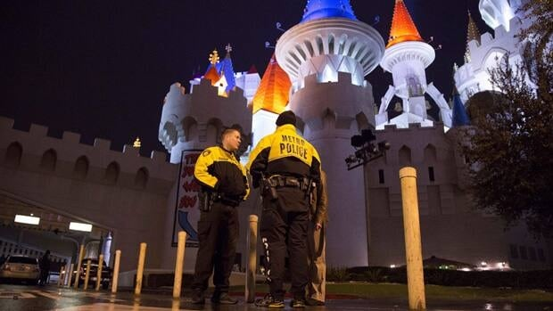 Las Vegas Metro Police officers stand watch Friday outside the entrance to the Excalibur hotel-casino after a shooting near the registration desk left two dead.