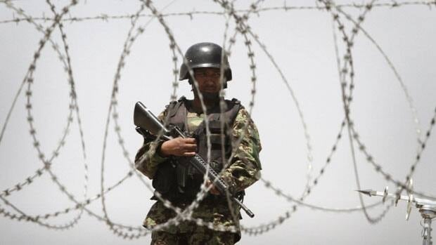 An Afghan soldier is seen through the barbed wires, standing guard at Kabul's airport in Afghanistan following a shooting incident on Wednesday.