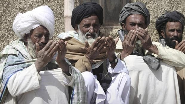 Afghan villagers take part in a prayer ceremony for victims of Sunday's killing of civilians, allegedly by a U.S. soldier, in Panjwai, Kandahar province south of Kabul, Afghanistan, on Tuesday.