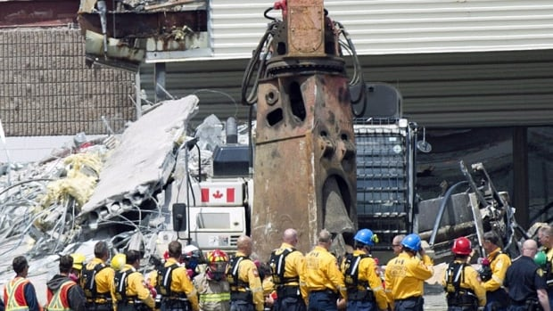 Rescue workers stand in a line and remove their hard hats as firefighters carry a second body out of the Algo Centre Mall in Elliot Lake, Ont., on June 27, 2012. A funeral for one of the victims in the collapse, Doloris Perizzolo, 70, is scheduled for next week.