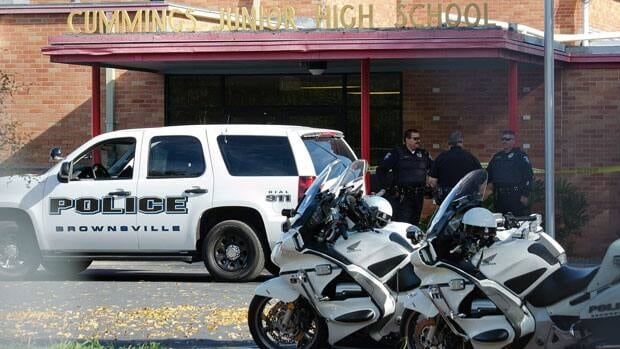 Police in Brownsville, Texas, stand in front of Cummings Middle School after officers shot and killed Grade 8 student Jamie Gonzalez, who brandished a weapon that turned out to be a pellet gun in the main hallway of his middle school Wednesday.