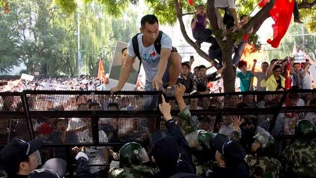 A Chinese demonstrator climbs over the fence outside the Japanese Embassy in Beijing on Saturday.