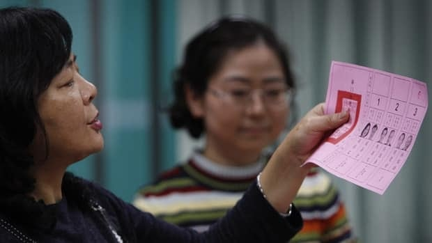 A worker displays a ballot as they count votes at a polling station in Taipei, Taiwan, on Saturday. Taiwanese voted Saturday in a closely fought presidential election that pits incumbent Ma Ying-jeou's vision of better relations with China against his main challenger's attempts to galvanize resentment over growing income inequality.