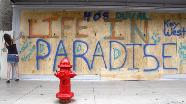 Shira Edllan Gervasi puts her name on plywood protecting a storefront in Key West, Fla., in anticipation of Isaac's wrath.