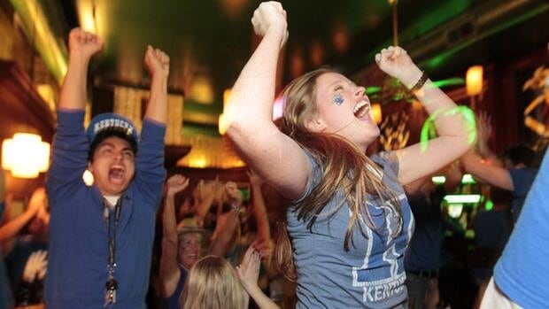 Kentucky student Alberto Velasco, left, and alumna Haley Nozell celebrate a first-half Kentucky lead over Kansas. After the game, celebrations would get out of hand on the streets of Lexington.