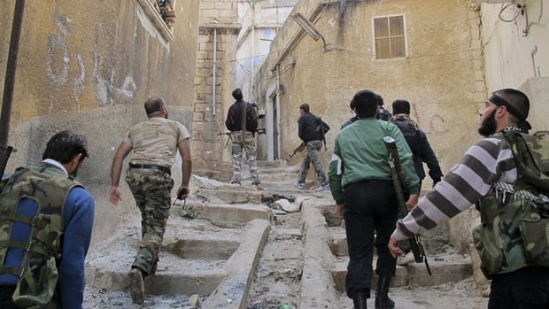 Members of the Free Syrian Army climb up stairs during a patrol in Haram town, Idlib Governorate on Tuesday.