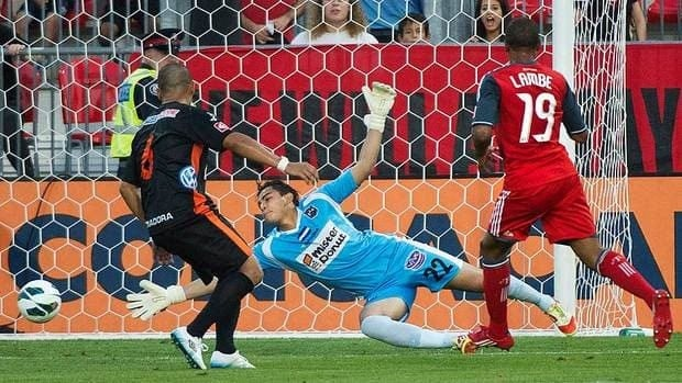Toronto FC forward Reggie Lambe shoots the ball past CD Aguila goalie Benji Villalobos during first half CONCACAF soccer action.