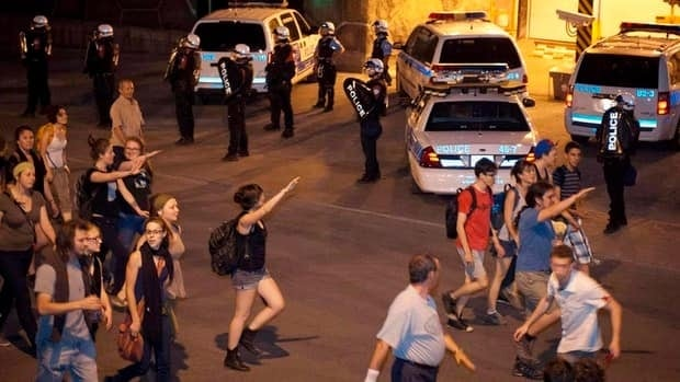 Protesters give riot officers the raised arm salute behind Quebec provincial police headquarters in Montreal in May.