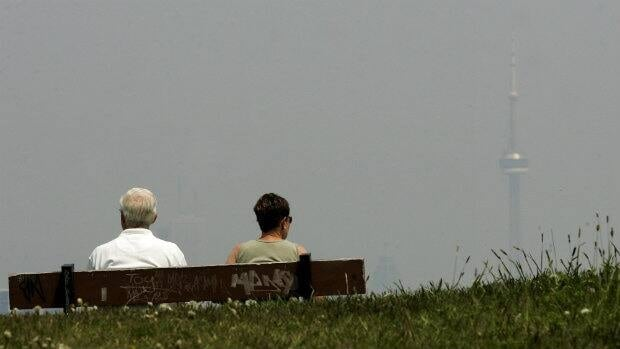 Robert Bonnell, left, and his wife Hilary Bonnell over look Toronto's hazy city skyline. A new national air pollution system could reduce the number of smog days in Canadian cities.