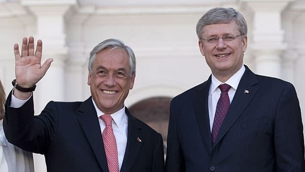Chilean President Sebastian Pinera, left, and Prime Minister Stephen Harper stand in front of the presidential palace in Santiago on Monday.