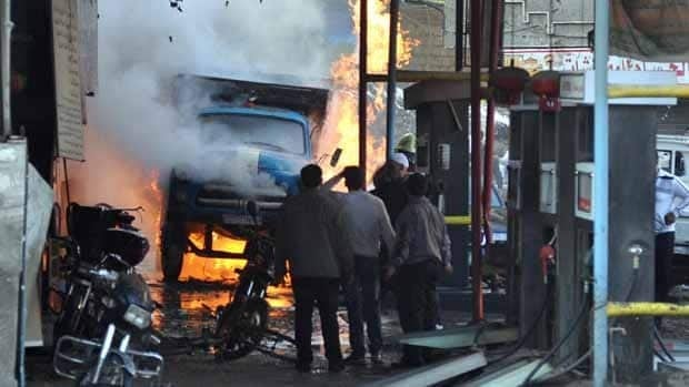 Syrian citizens stand near a burning truck that was destroyed in Wednesday's bomb attcks.