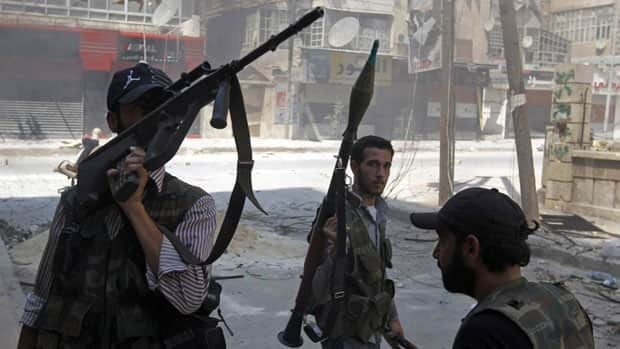 Free Syrian Army fighters hold their weapons during clashes in the Salaheddine neighbourhood of central Aleppo.
