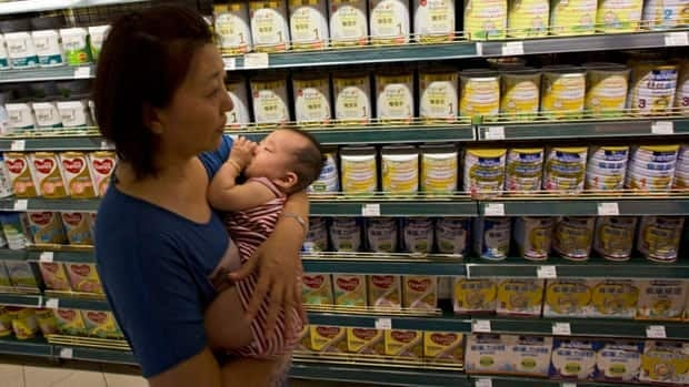 A Chinese woman carries a child past powdered milk products from New Zealand already inspected and deemed to be safe at a supermarket in Beijing.
